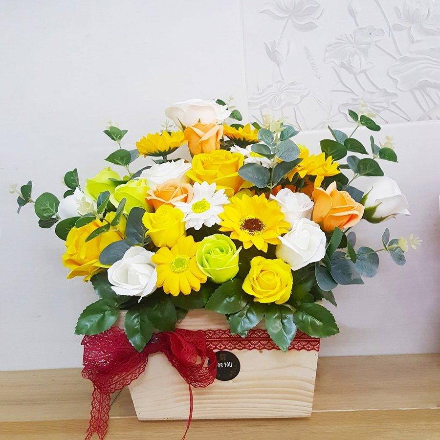 Chậu hoa sáp thơm gỗ sắc vàng và lá xanh